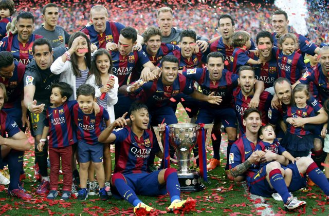 epa04764346 FC Barcelona's players pose with the Liga champions trophy after the Spanish Primera Division soccer match played against Deportivo at Camp Nou stadium in Barcelona, northeastern Spain, 23 May 2015. Xavi leaves the FC Barcelona. EPA/ANDREU DALMAU