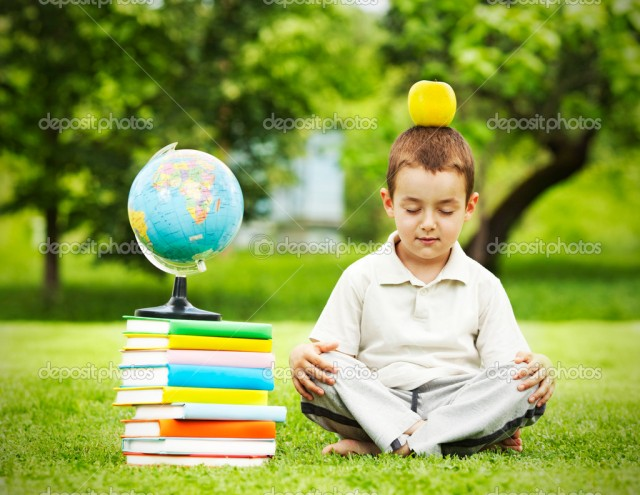 Little boy in zen meditation preparing to be good student with apple on the head